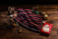 Knitted scarf with black, white and red stripes, Christmas decorations and a metal box with a picture of Santa Claus on a wooden royalty free stock photography