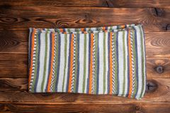 Knitted scarf with colored stripes on wooden background. Knitted scarf with colored stripes on a wooden background royalty free stock photo