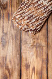 Knitted scarf on old wooden burned table or board for background Stock Images