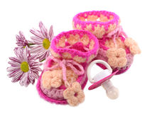 Knitted shoes with flowers and pacifier Stock Photography