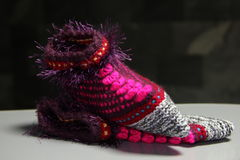Knitted shoes. Slipper socks related hands of colored woolen yarns Royalty Free Stock Photography