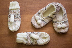 Knitted slippers with pompoms and mittens Stock Photos
