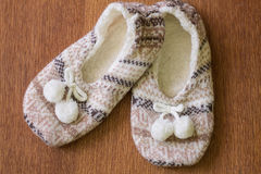 Knitted slippers with pompoms Stock Photo