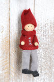 Knitted small Christmas handmade doll. Handmade Christmas decoration. Christmas Toy hanging on wooden background Royalty Free Stock Photo