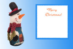 Knitted snowman with a card on a background of blue Christmas Stock Photos