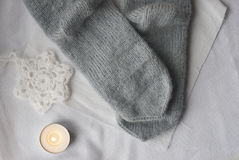 Knitted socks and crocheted snowflake Royalty Free Stock Images