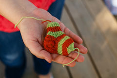 Knitted socks for premature babies in the hands Royalty Free Stock Photography
