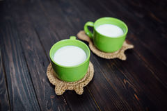 Knitted stand hot dishes and tea cups with , milk. Lying on a ba Royalty Free Stock Photography