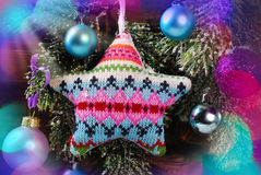 Knitted star decoration on christmas tree Royalty Free Stock Photography