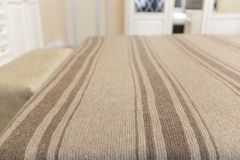 Knitted, striped bedspread on the bed in a light interior. Camel`s wool is brown stock photos