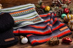 Knitted striped striped scarves, black knitted sleeves and Christmas toys on wooden background royalty free stock photo