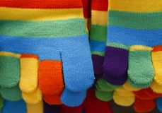Knitted striped winter gloves in bright colors Royalty Free Stock Images