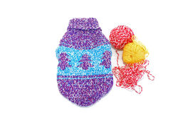 Knitted sweater for a dog with two balls of wool yarn. Knitted sviterok of handwork for a little dog with two balls of threads. A white background, it is Royalty Free Stock Images