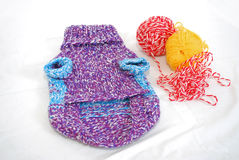 Knitted sweater for a little dog with two balls of wool yarn. Knitted sviterok for a dog with two balls of wool yarn Royalty Free Stock Photos