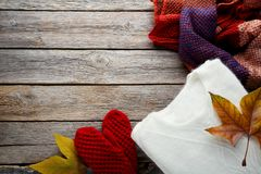 Knitted sweater, scarf and gloves. Stack of knitted sweater, scarf and gloves with autumn leafs royalty free stock image