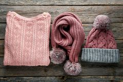 Sweater, scarf and hat. Knitted sweater, scarf and hat on wooden table stock photo