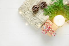Knitted sweater sweater gift box pine cones green juniper twig golden lights garland candle on wood. Christmas royalty free stock image