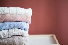 Knitted sweaters folded in a pile stock photography