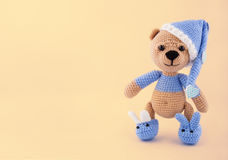 Knitted teddy bear in a cap and slippers on a gentle yellow background. Toys made by hand. A soft gift. Copy space. Knitted teddy bear in a cap and slippers on a Royalty Free Stock Photos