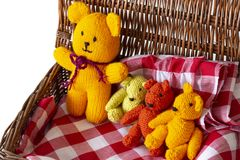 Knitted teddy bear toys on gingham fabric material in a wicker picnic basket. Teddy bears picnic concept stock photography