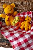 Knitted teddy bear toys on gingham fabric material in a wicker picnic basket. Teddy bears picnic concept royalty free stock photography