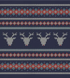 Knitted  texture on blue background with deers Stock Images
