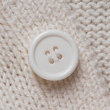 Knitted texture with a white button Stock Image