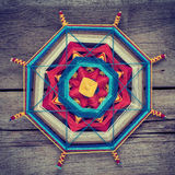 Knitted tibetan mandala from threads on wooden background Stock Images