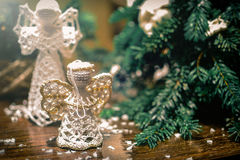 Knitted toy angels beside Christmas tree stock photo