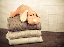 Knitted toy dog on the stack of knitted clothes on wooden table Stock Images