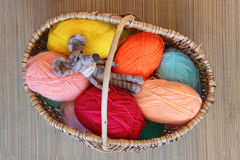Knitted toy mouse is mottled in a wicker basket among the skeins Royalty Free Stock Image