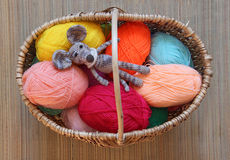 Knitted toy mouse is mottled in a wicker basket among the skeins Stock Image