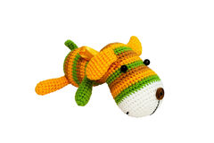 Knitted toy - striped lying dog. Royalty Free Stock Photography