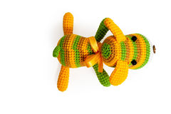 Knitted toy - striped lying dog. Stock Images