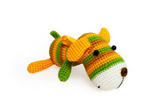 Knitted toy - striped lying dog. Stock Photos