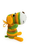 Knitted toy - striped sitting dog. Stock Photos