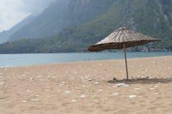 Knitted umbrella on beach. Sea Stock Photos