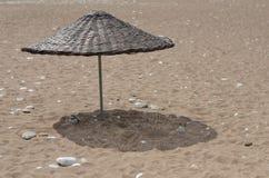 Knitted umbrella on beach. Sea Stock Photo