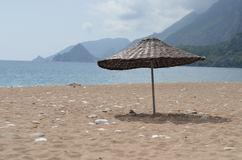 Knitted umbrella on beach. Sea Royalty Free Stock Photo