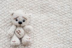 A knitted white bear is lying on a light knitted handmade fabric. There is a free space royalty free stock photography