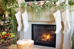 Knitted white Christmas stockings hanging on a fireplace mantle stock photo