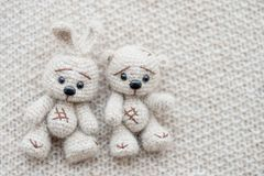 Knitted white hare and bear. A knitted white hare and bear are lying on a light knitted handmade fabric. There is a free space stock photos