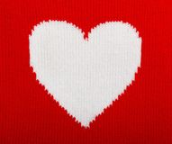 Knitted white heart on red Stock Photography