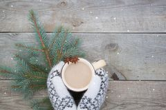 Knitted white wool mittens with a cup of coffee cocao on the wooden background. Knitted wool mittens with a cup of coffee cocao on the wooden background. Rustic Stock Photography