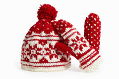 Knitted winter cap and mittens. on white. Winter cap and mittens knitted with jackard and heart motifs. on white Royalty Free Stock Photos