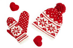 Knitted winter cap and mittens. on white. Winter cap and mittens knitted with jackard and heart motifs. on white Royalty Free Stock Image