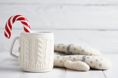 Knitted winter cup with candy cane Royalty Free Stock Photos