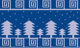 Knitted Winter Theme with Fir Trees and Snow on Blue. Knit fir tree forest in winter snow on blue Stock Photo