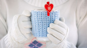 Knitted wool cup. In human hands. With red hearts Stock Images
