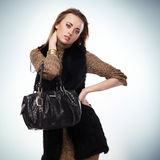 Knitted wool dress. Woman with a bag in knitted wool dress and fur vest on light-blue background Stock Photos
